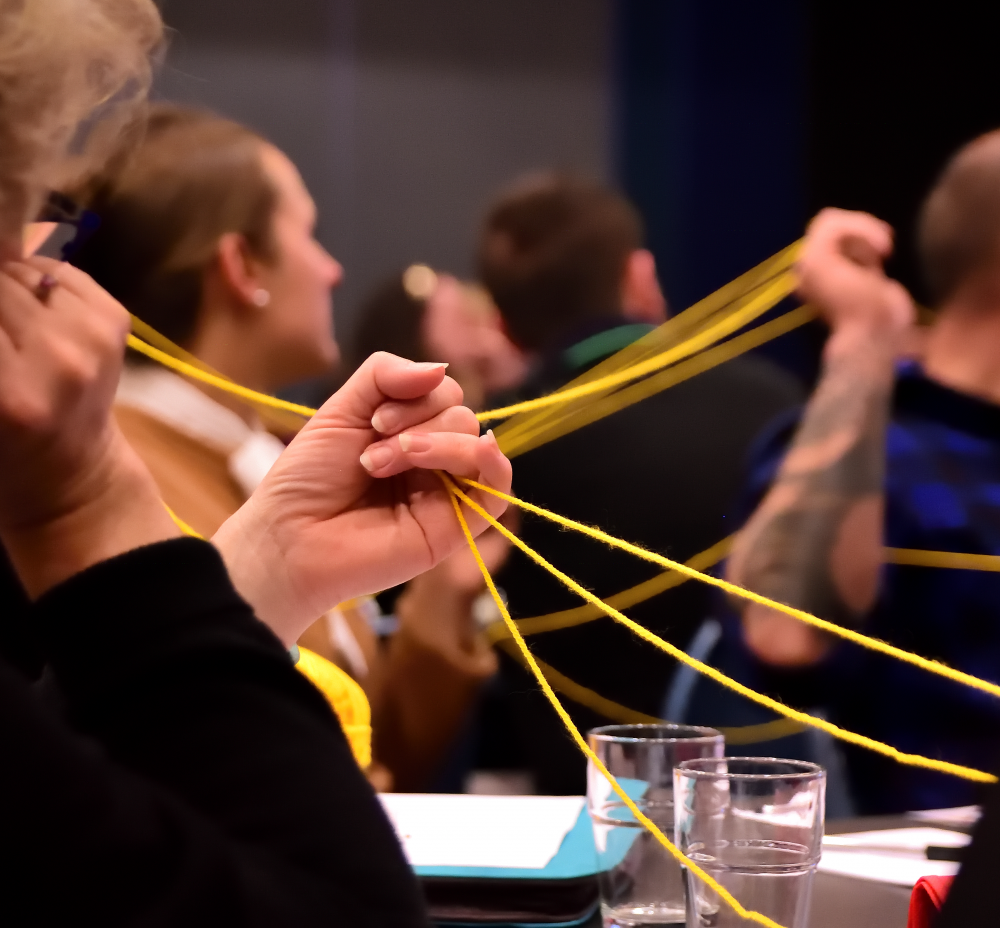 Blurred image of a group of people listening to a speaker. They hold their hands up, holding connected strings of wool.